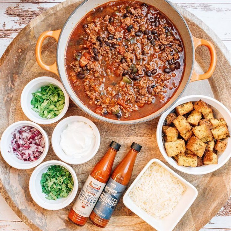 chorizo and black bean chili and condiments on a round board