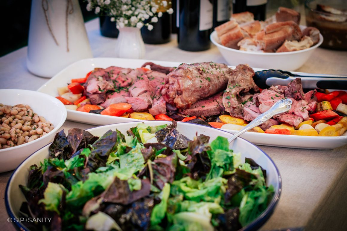 a salad, lamb dish and bread on a table