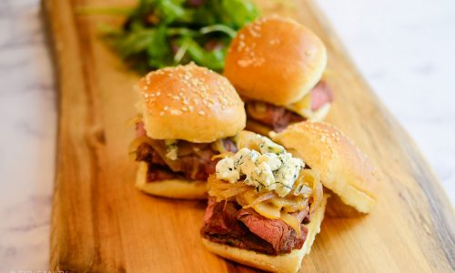steak sliders with caramelized pears, onions and gorgonzola on a board