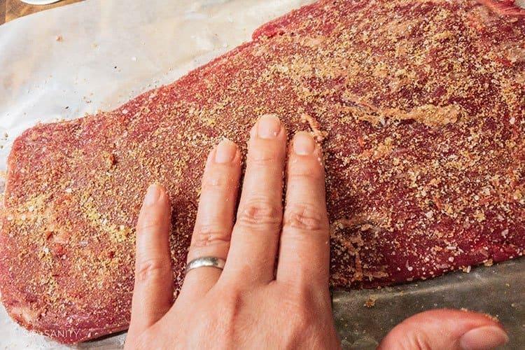 flank steak with seasonings being applied