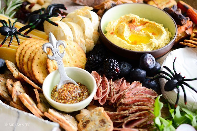 bowls of mustard and hummus with salami and crackers