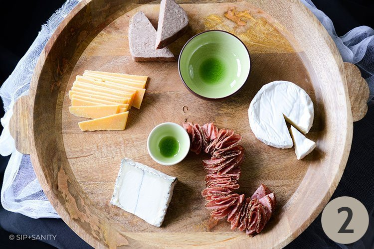 wood board with bowls, cheese and salami
