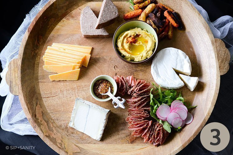 wood board with meat, cheese and veggies