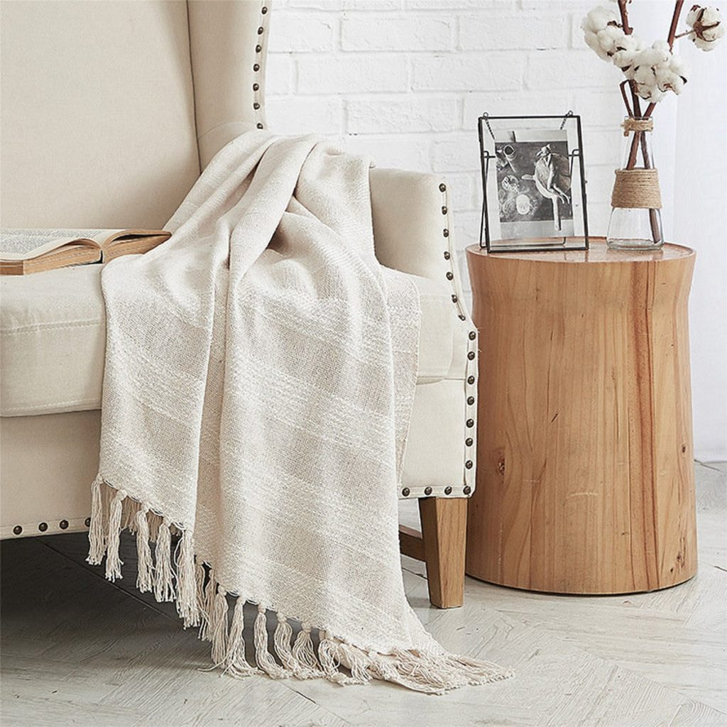 blanket draped over a chair next to a side table