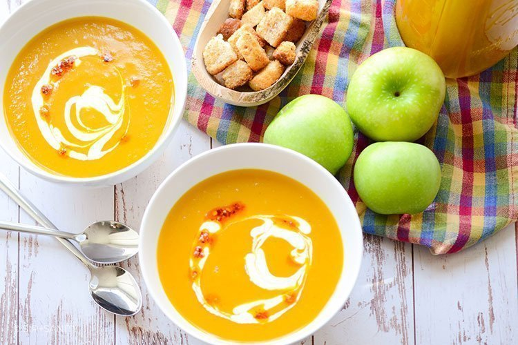 two bowls of curried butternut squash and granny smith soup with croutons, apples and a jar