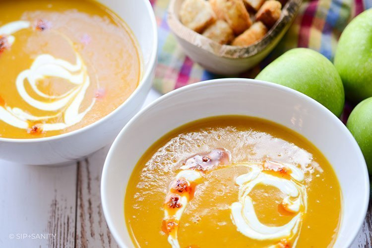 bowls of curried butternut squash and granny smith soup next to apples and croutons