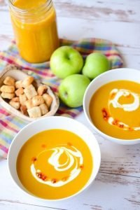 bowls of soup next to apples, croutons and a jar