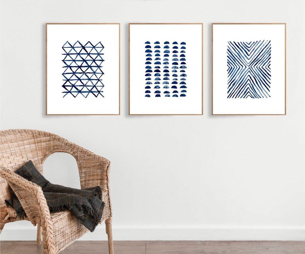 three blue and white abstract prints hanging on a wall