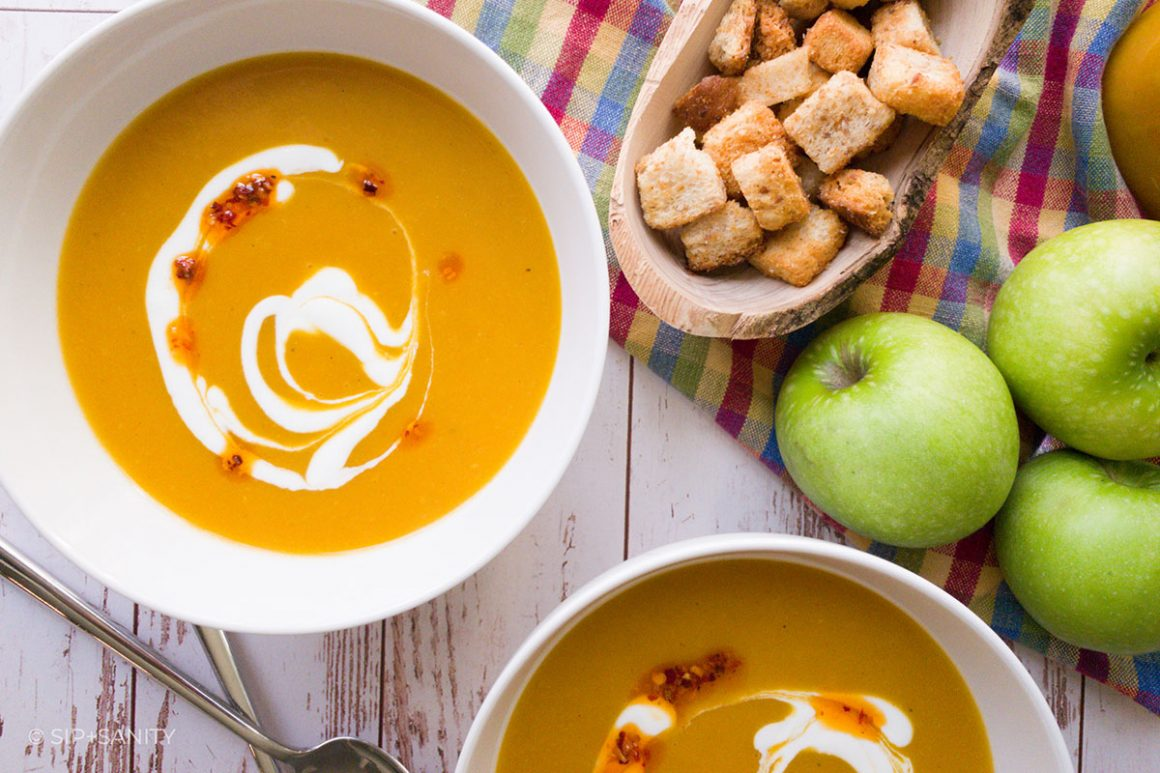 bowls of curried butternut squash and granny smith soup next to croutons and apples