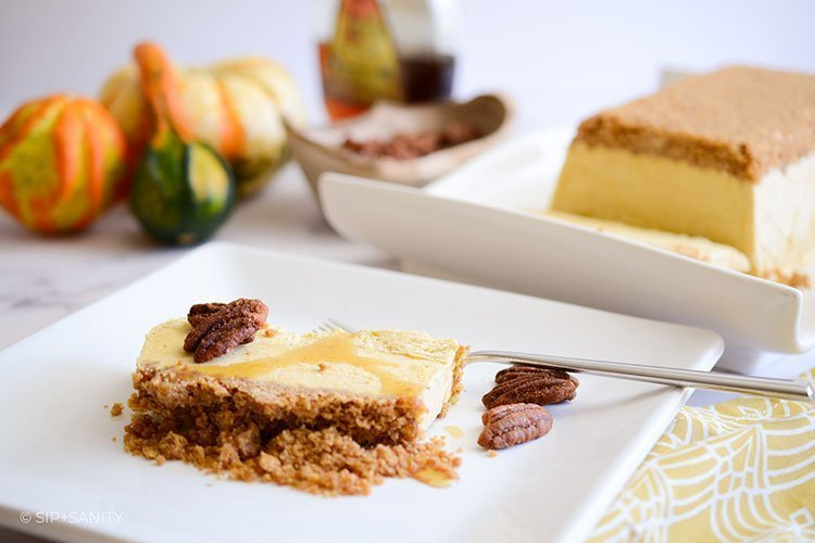 slice of pumpkin and maple semifreddo with graham cracker streusel on a plate with objects in the background