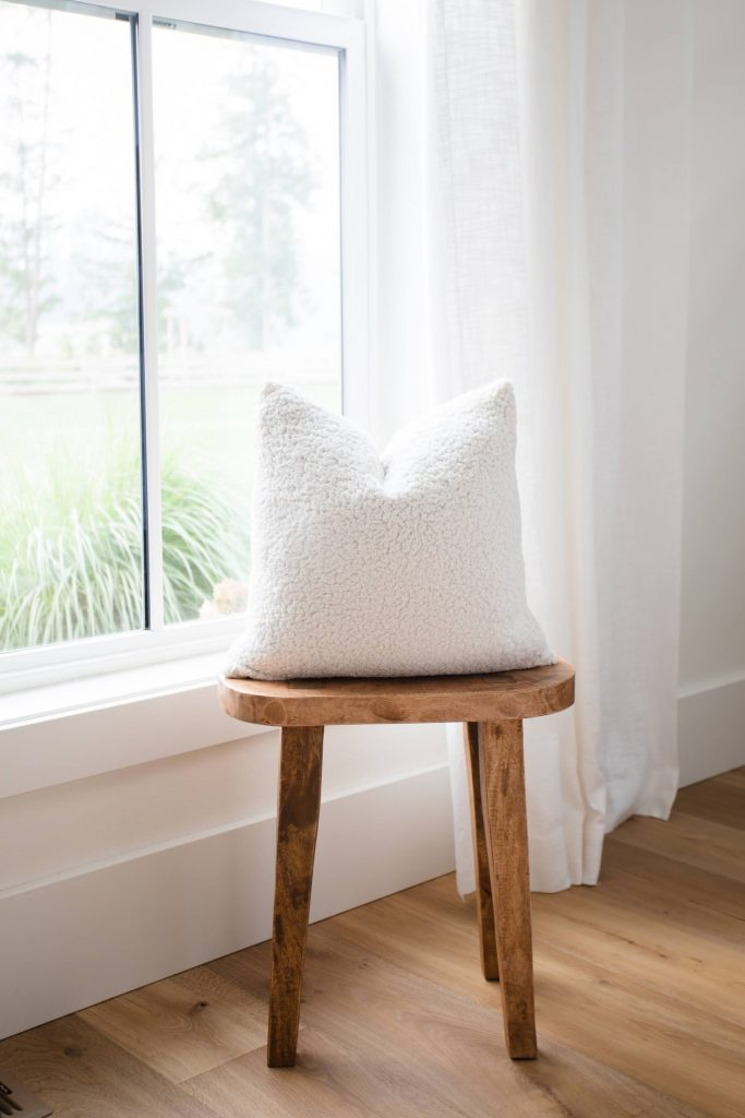 sherpa pillow on a stool in front of a window