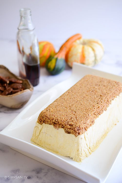 pumpkin and maple semifreddo with graham cracker streusel on a serving platter with objects in the background