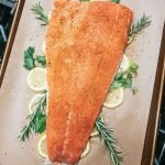 filet of salmon on a bed of herbs and lemons