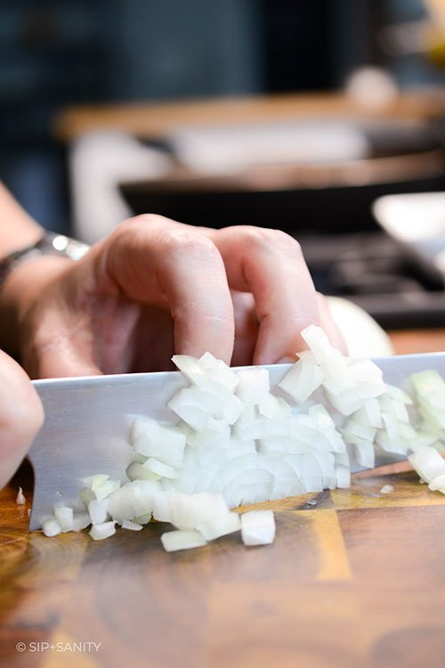 hand chopping onions with a knife