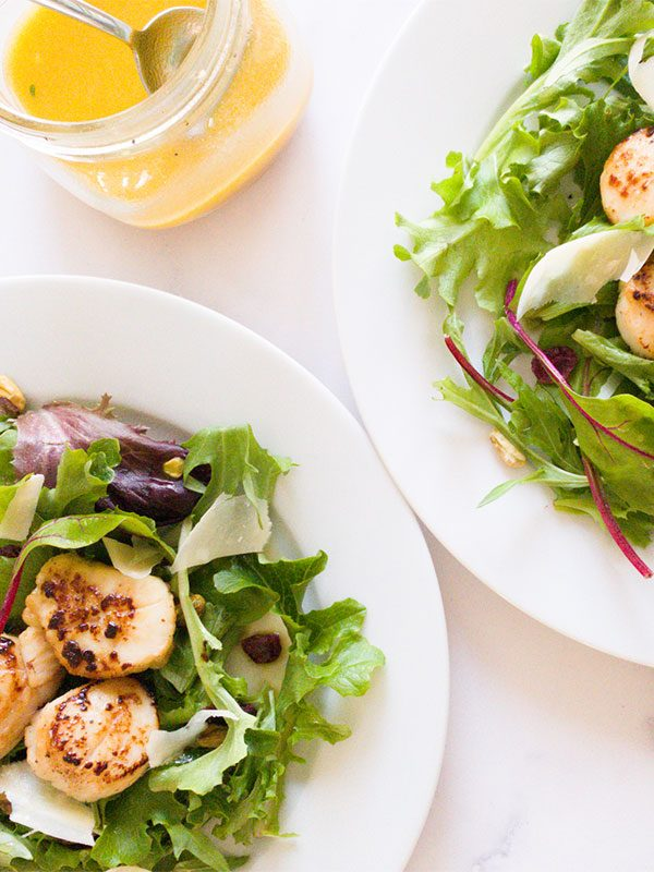 two plates with salad and scallops