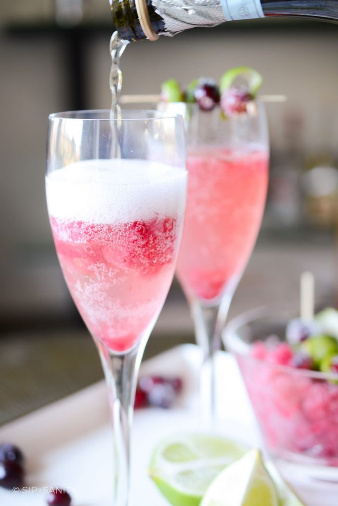 prosecco being poured into a glass of cranberry-lime natale sparkler