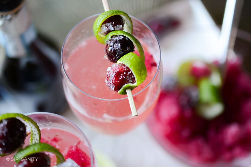 closeup of a cranberry-lime natale sparkler with lime zest and cranberry garnish