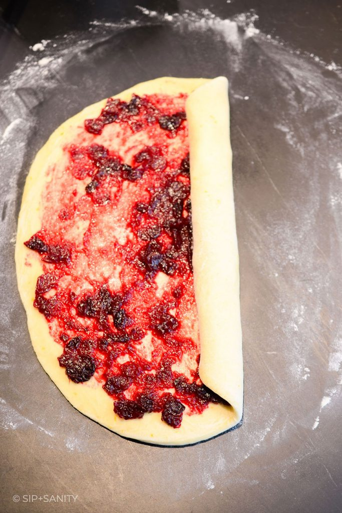 cranberry filling on dough being rolled up