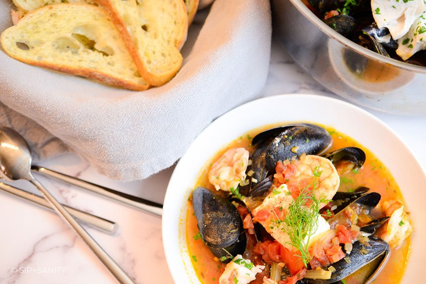 basket of ciabatta bread and a bowl of seafood stew