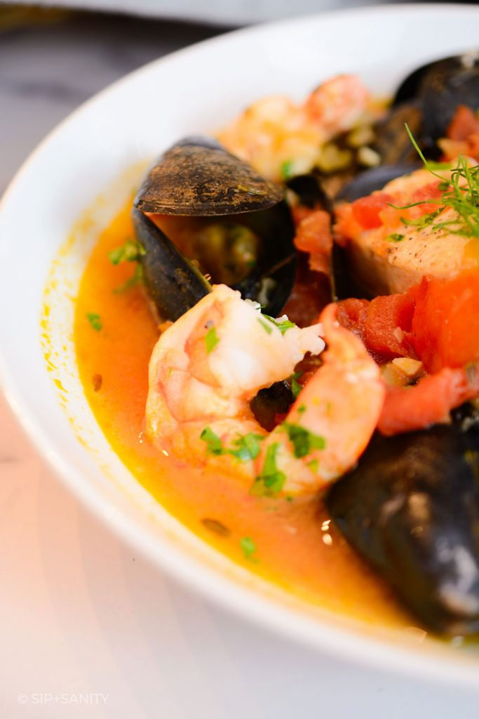 close up bowl of tomato based seafood stew