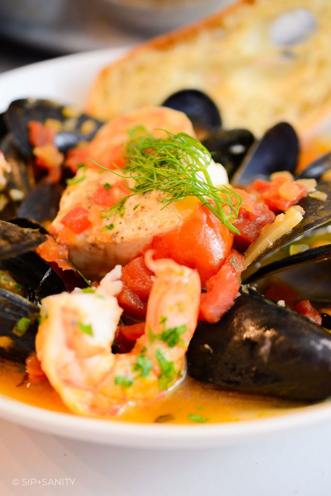 bowl of tomato based seafood stew with shrimp, fish, and mussels