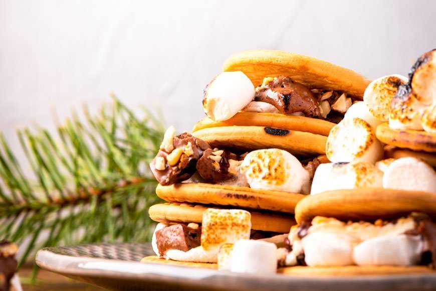 a stack of holiday s'mores with a pine branch in the background