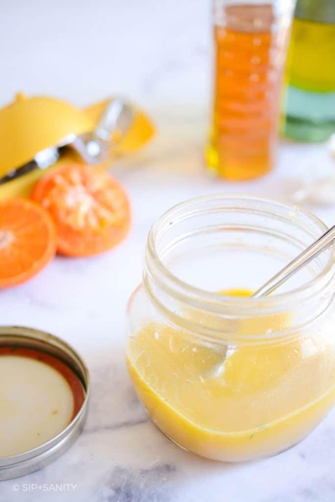 jar of vinaigrette, an orange, and bottles of honey and oil