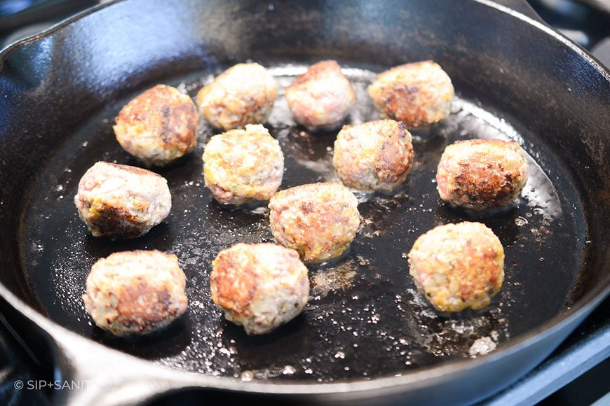 meatballs browning in a cast iron skillet