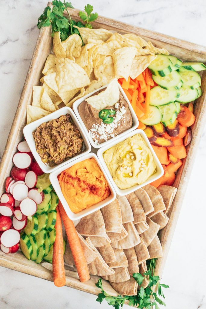 a snack board with easy homemade hummus, raw veggies, chips and pita bread