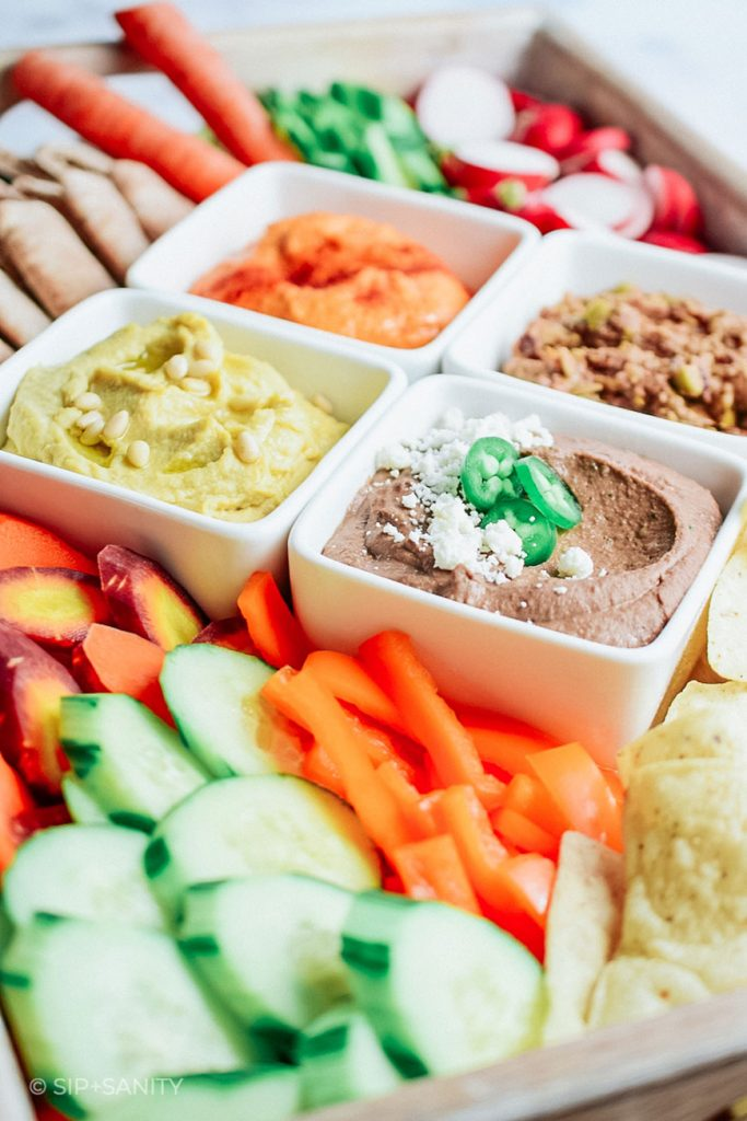 snack board with three kinds of hummus, veggies and chips
