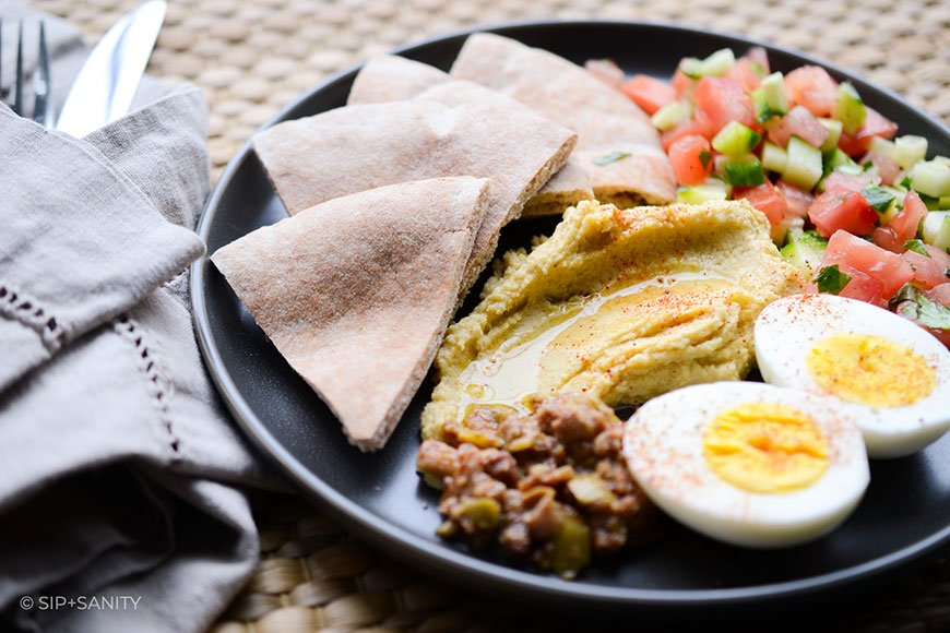 pita bread, hummus, hard cooked egg and chopped vegetables on a plate
