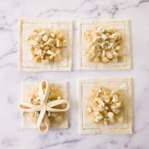 four squares of pastry with pear filling, one being folded into a design