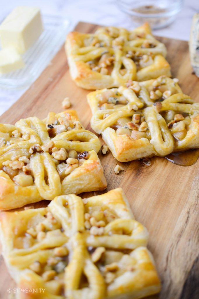 four cashel blue cheese and pear tarts on a wooden board