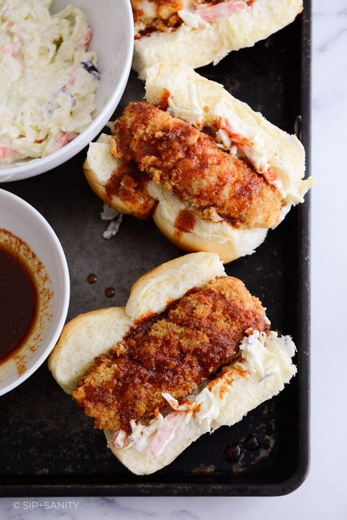 a tray with three air fryer spicy fish sandwiches, and bowls of slaw and vinaigrette