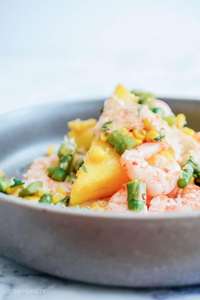 bowl of shrimp and polenta cakes with sundried tomato cream sauce
