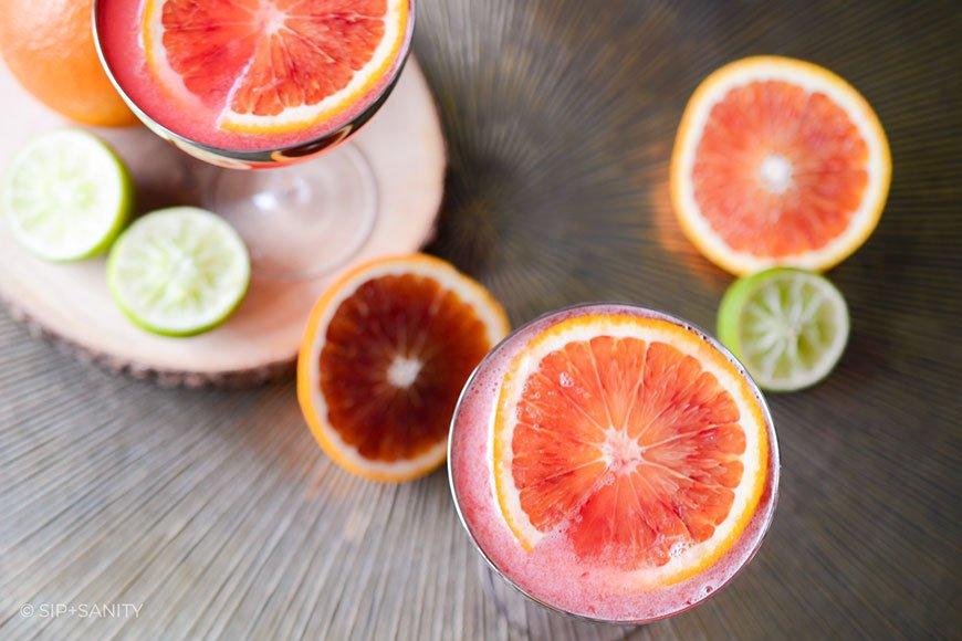 overhead shot of blood oranges, limes and cocktails
