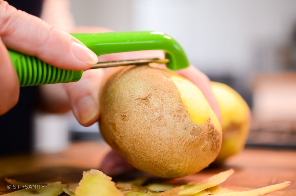 potato being peeled with a vegetable peeler