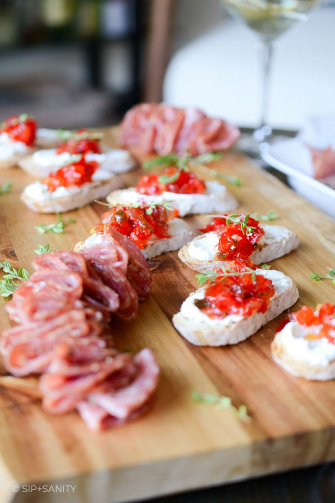 wood board with salami and goat cheese crostini