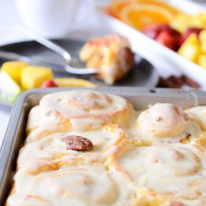 cinnamon rolls in a pan with fruit in the background