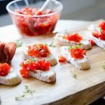 goat cheese and red pepper bruschetta on a serving board