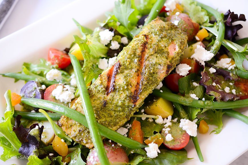 plate of salad with basil dressing and grilled salmon