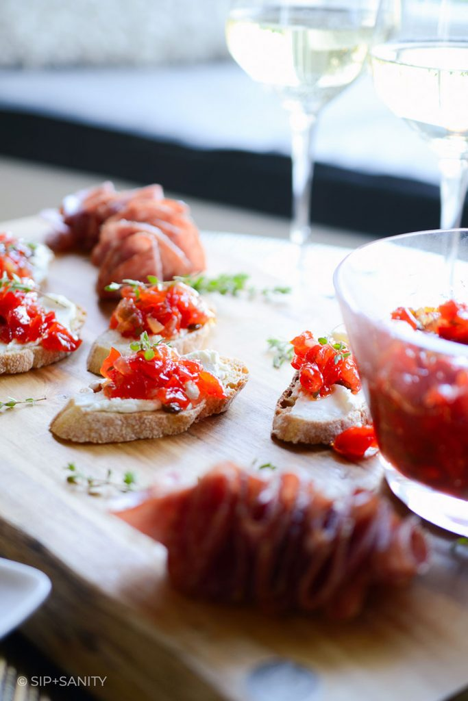 wooden board with red pepper jam crostini and white wine glasses