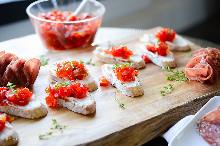 wood board with toasted bread topped with goat cheese and red pepper jam