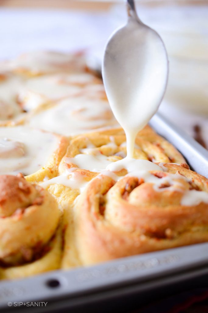 cream cheese icing being poured on sweet rolls