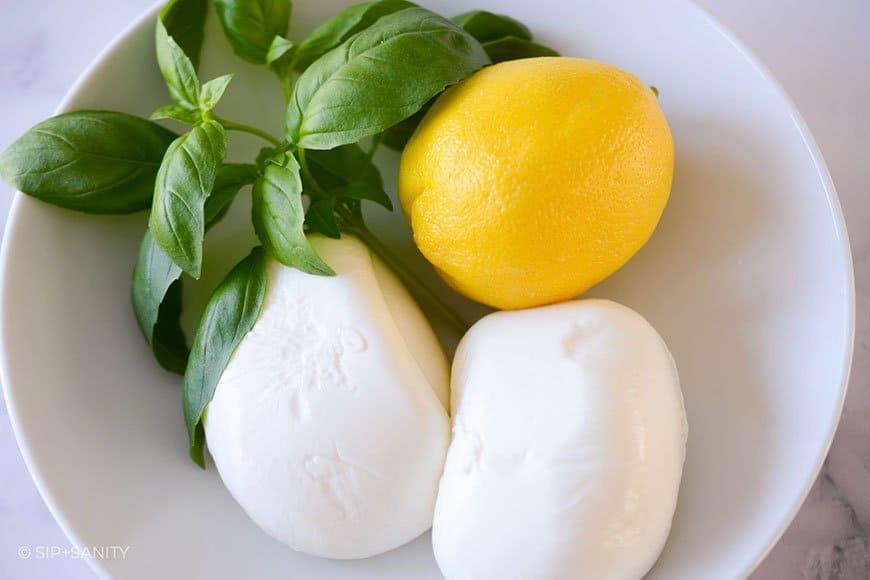 two balls of burrata with a lemon and fresh basil