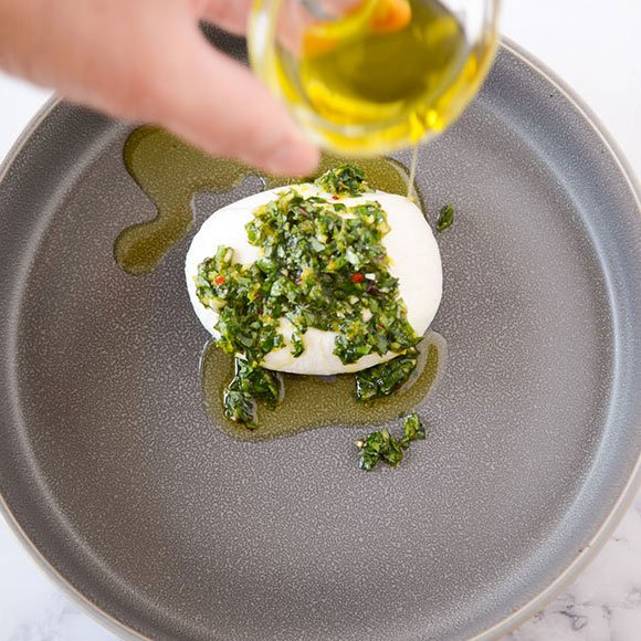 drizzling olive oil over basil and lemon burrata