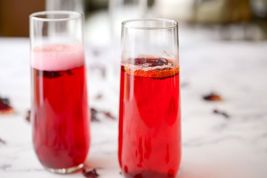 two glasses of hibiscus tea mimosas on a marble table