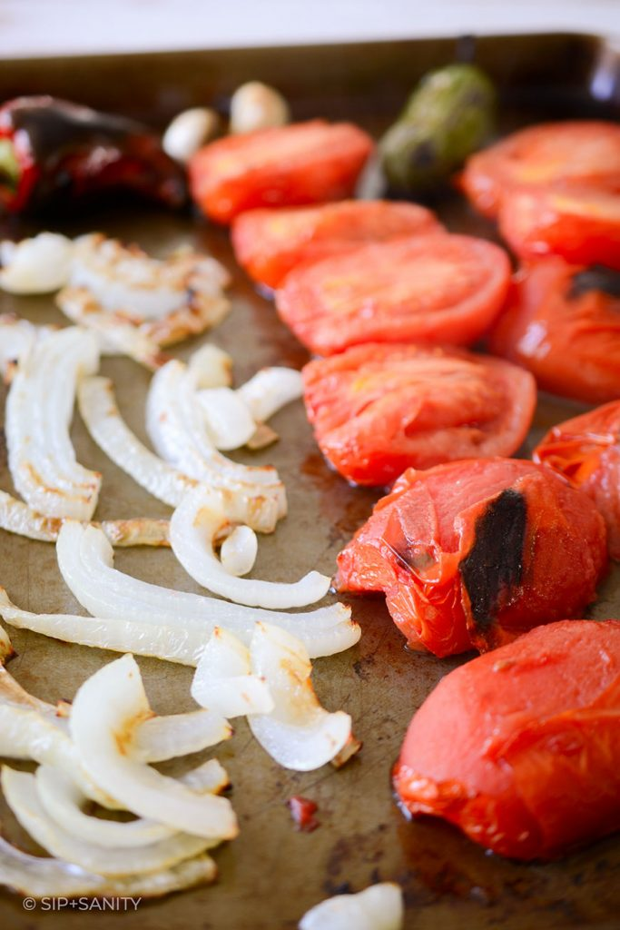 roasted onions, tomatoes, chili peppers and garlic on a sheet pan