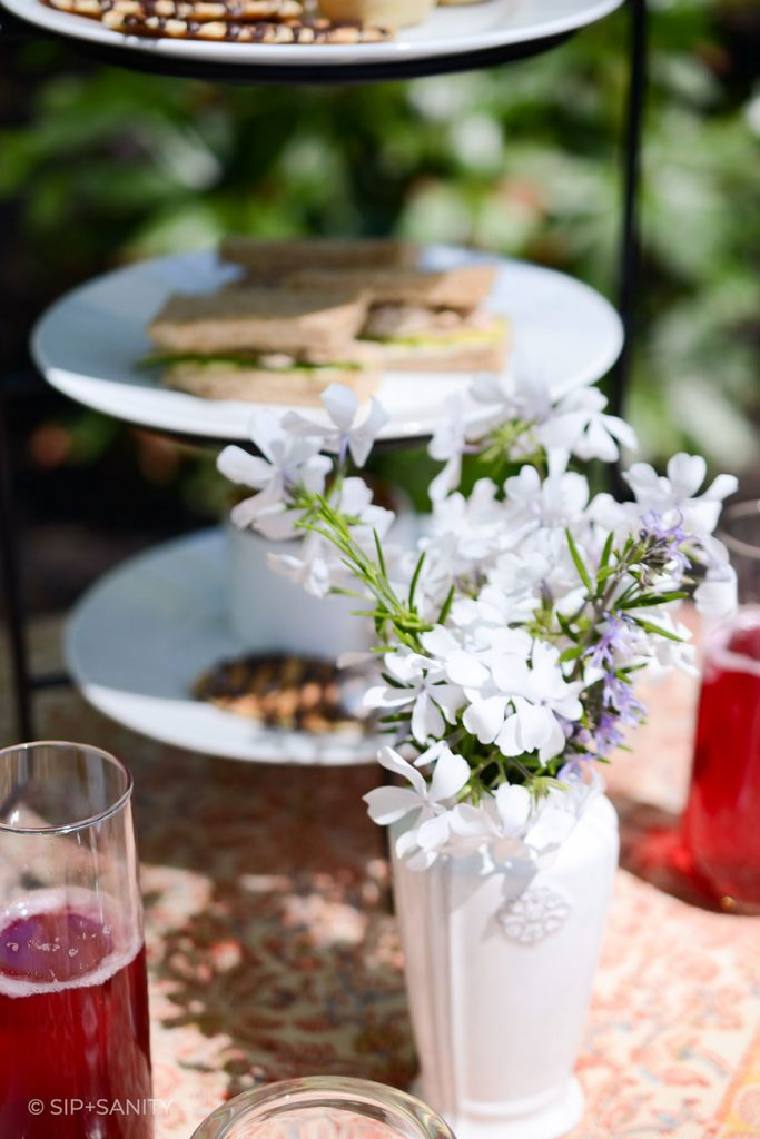 a tea table with flowers, mimosas and snacks