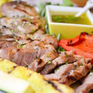 sliced pork steaks with grilled veggies and bowl of vinaigrette